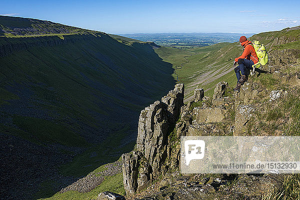 A man hiking the Pennine Way sits on the edge of the huge escarpment called Highcup Nick in the Yorkshire Dales  Yorkshire  England  United Kingdom  Europe
