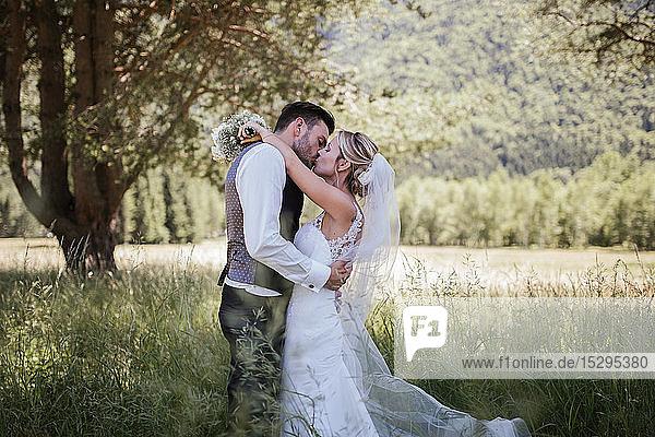 Romantisches Paar küsst sich am Hochzeitstag im Wald  Stresa  Piemont  Italien
