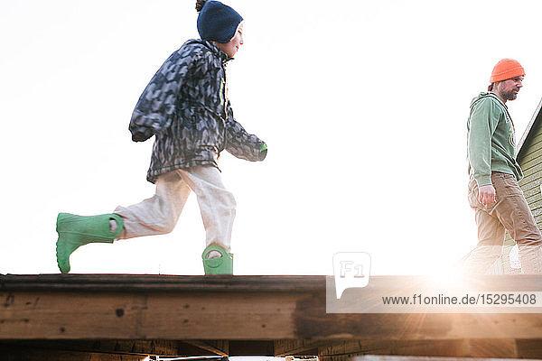 Junge mit Vater läuft über die sonnenbeschienene Skateboard-Rampe  Blickwinkel niedrig
