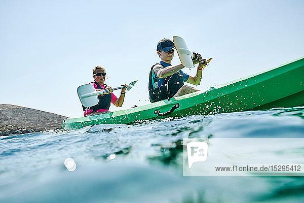 Teenager Junge und Mutter beim Seekajakfahren  oberflächennahe Seitenansicht  Limnos  Khios  Griechenland Teenager Junge und Mutter beim Seekajakfahren, oberflächennahe Seitenansicht, Limnos, Khios, Griechenland