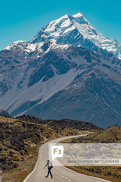 Hiker crossing road leading towards mountains  Wanaka  Taranaki  New Zealand