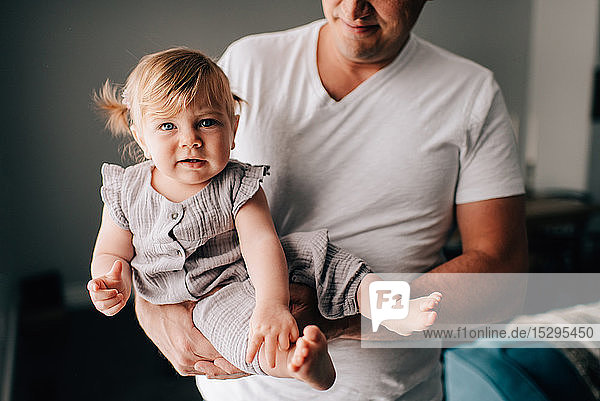 Vater  der eine kleine Tochter auf dem Arm trägt  beschnittenes Porträt