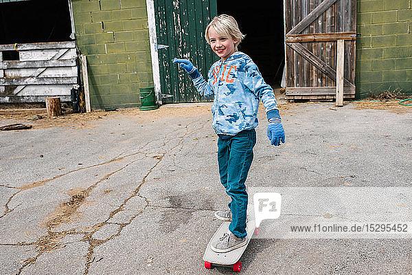 Blonder Junge fährt Skateboard auf dem Bauernhof