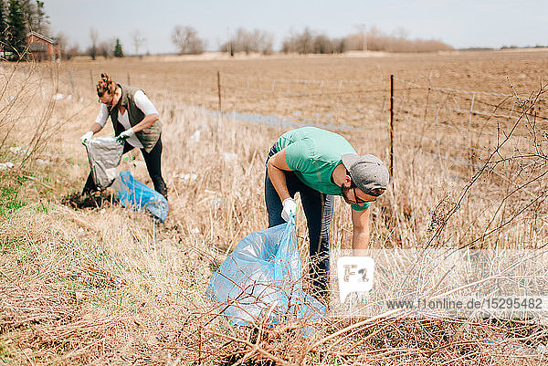 Couple picking up rubbish by field  Georgetown  Canada
