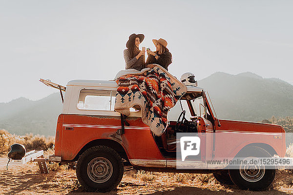 Friends toasting on rooftop of off road vehicle  Kennedy Meadows  California  US