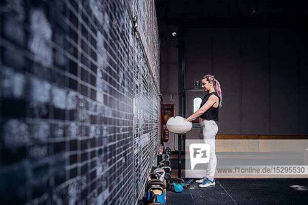 Young woman powdering palms in gym