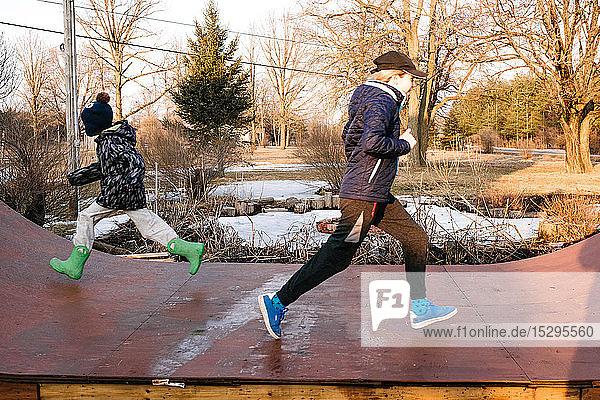 Mädchen und Bruder laufen auf einer ländlichen Skateboard-Rampe in entgegengesetzte Richtungen