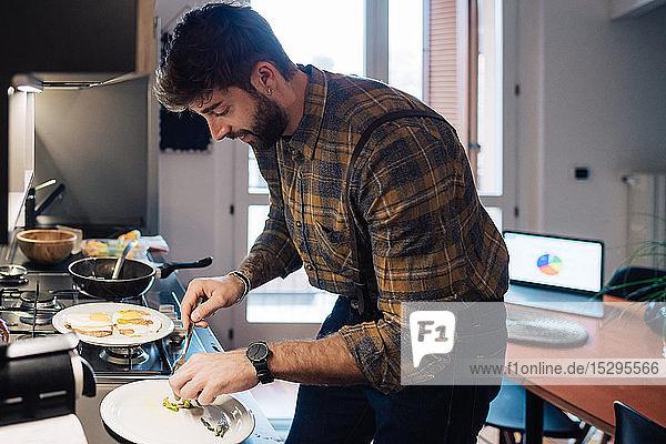 Mid adult man plating food at kitchen counter