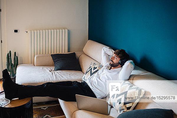Mittelgroßer erwachsener Mann  der auf dem Sofa liegt und Kopfhörer hört