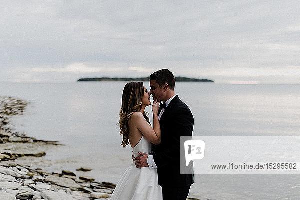 Romantische junge Braut und Bräutigam von Angesicht zu Angesicht am Seeufer