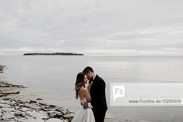 Romantische junge Braut und Bräutigam umarmen sich am Hochzeitstag am Seeufer