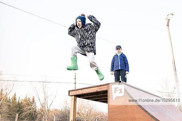 Mädchen sieht Bruder beim Sprung von der Skateboard-Rampe