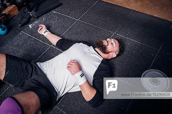 Erschöpfter junger Mann macht Pause im Fitnessstudio