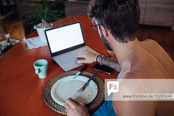Mid adult man typing on laptop at breakfast table
