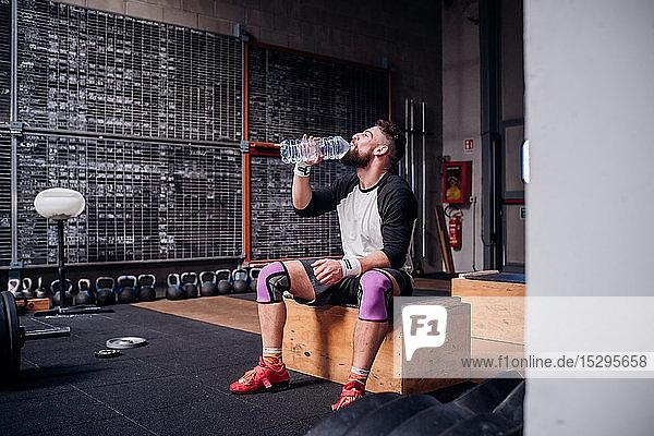 Junger Mann trinkt Wasser im Fitnessstudio