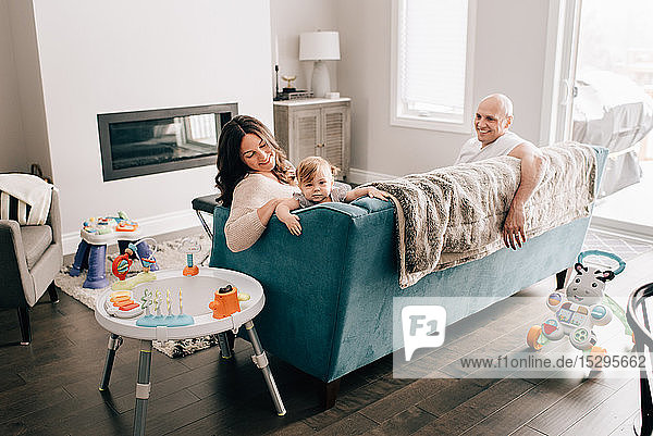 Mother and father reclining on sofa with baby daughter