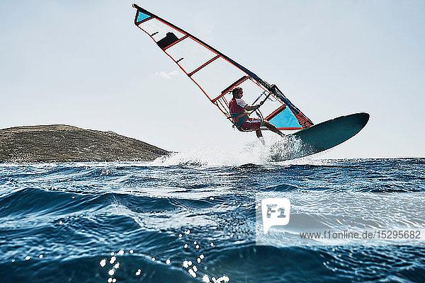 Junger Mann in der Luft beim Windsurfen auf Meereswellen  Limnos  Khios  Griechenland Junger Mann in der Luft beim Windsurfen auf Meereswellen, Limnos, Khios, Griechenland