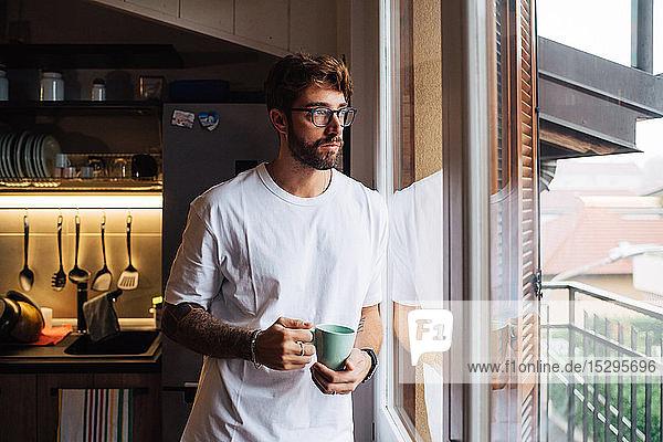 Mittelgroßer erwachsener Mann mit Kaffeetasse  der durch das Wohnungsfenster hinausblickt