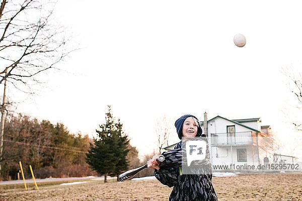 Junge schlägt Baseball auf ländlichem Feld  Aktion