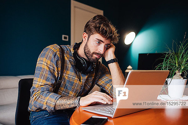 Mid adult man sitting at living room table looking at laptop