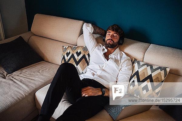 Mittelgroßer  auf dem Sofa liegender Mann  der mit geschlossenen Augen Kopfhörer hört
