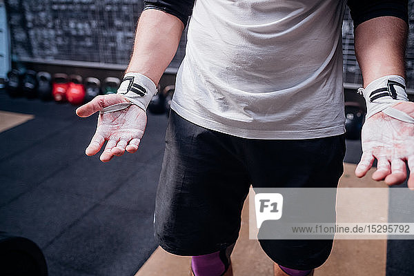 Young man showing powdered palms in gym