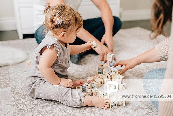 Mutter und Vater auf der Kindertagesstätte  während die kleine Tochter mit Bauklötzen spielt  ausgeschnitten