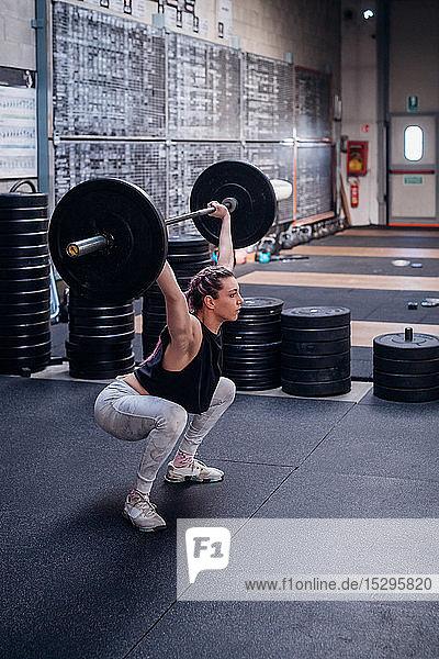 Junge Frau hebt Langhantel im Fitnessstudio