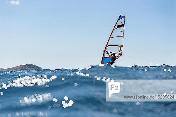 Junger Mann beim Windsurfen auf Meereswellen  Blick auf die Oberfläche  Limnos  Khios  Griechenland Junger Mann beim Windsurfen auf Meereswellen, Blick auf die Oberfläche, Limnos, Khios, Griechenland
