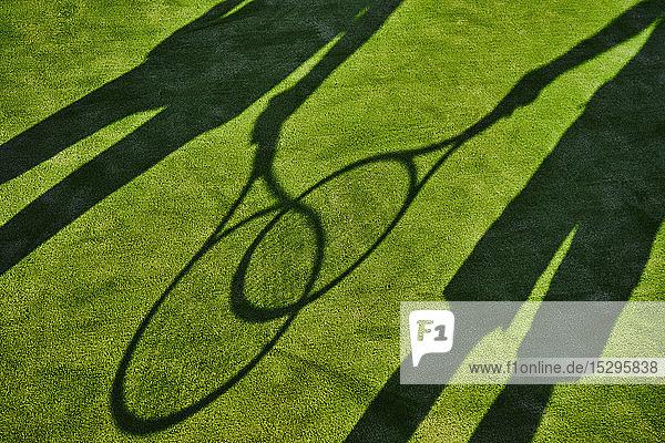 Angeschnittene Schatten von zwei Tennisspielern mit Tennisschlägern auf grünem Rasen Angeschnittene Schatten von zwei Tennisspielern mit Tennisschlägern auf grünem Rasen