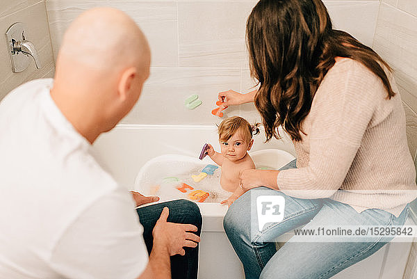 Mutter und Vater spielen mit der kleinen Tochter in der Badewanne  Blick über die Schulter