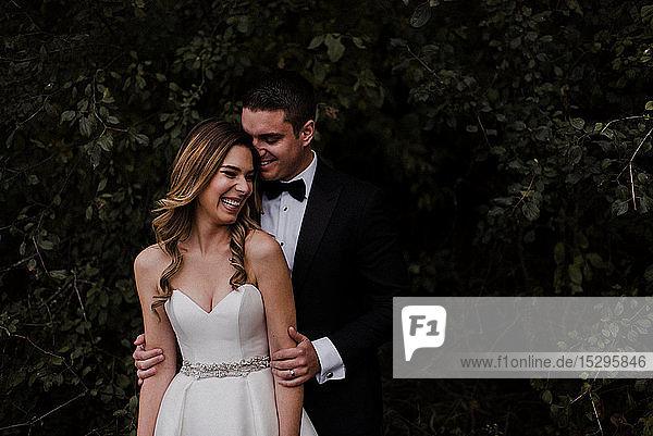 Glückliche junge Braut und Bräutigam lachend vor dem Laub