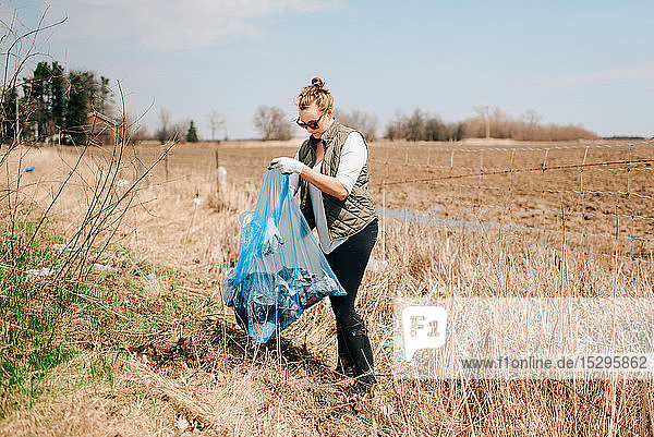 Woman picking up rubbish by field  Georgetown  Canada