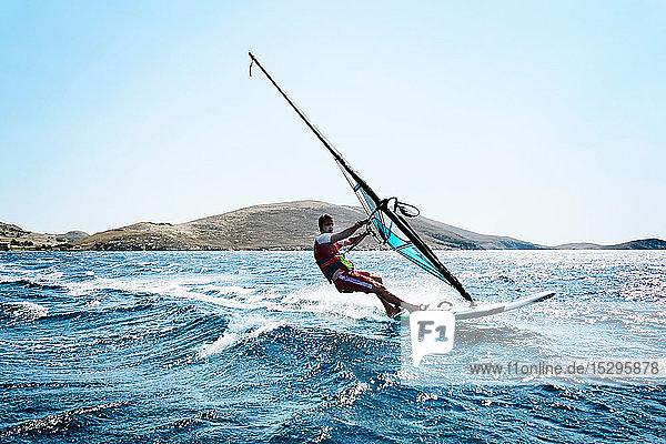 Junger Mann beim Windsurfen auf Meereswellen  Seitenansicht  Limnos  Khios  Griechenland Junger Mann beim Windsurfen auf Meereswellen, Seitenansicht, Limnos, Khios, Griechenland