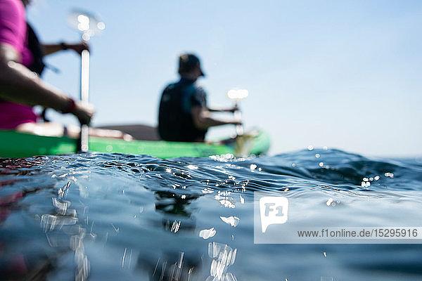 Teenager Junge und Mutter beim Seekajakfahren  Oberflächenniveau flacher Fokus Seitenansicht  Limnos  Khios  Griechenland Teenager Junge und Mutter beim Seekajakfahren, Oberflächenniveau flacher Fokus Seitenansicht, Limnos, Khios, Griechenland