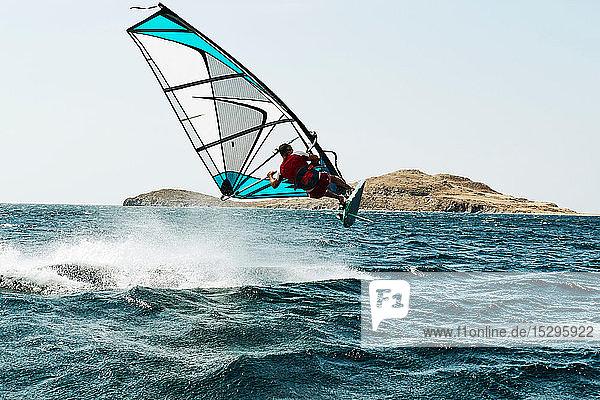 Junger Mann beim Windsurfen über der Meereswelle  Rückansicht  Limnos  Khios  Griechenland Junger Mann beim Windsurfen über der Meereswelle, Rückansicht, Limnos, Khios, Griechenland