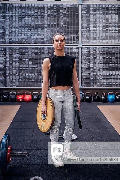 Junge Frau trägt Hantelscheiben im Fitnessstudio