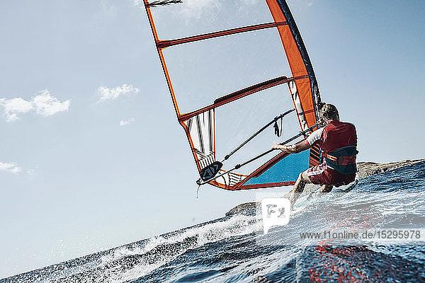 Junger Mann lehnt sich zurück und surft auf den Wellen des Ozeans  Schrägansicht  Limnos  Khios  Griechenland Junger Mann lehnt sich zurück und surft auf den Wellen des Ozeans, Schrägansicht, Limnos, Khios, Griechenland