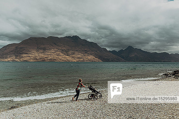 Mother with baby in pram walking on beach  Queenstown  Canterbury  New Zealand