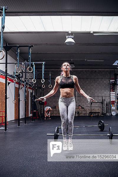 Junge Frau springt im Fitnessstudio
