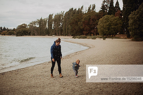 Mother and baby walking on beach  Wanaka  Taranaki  New Zealand
