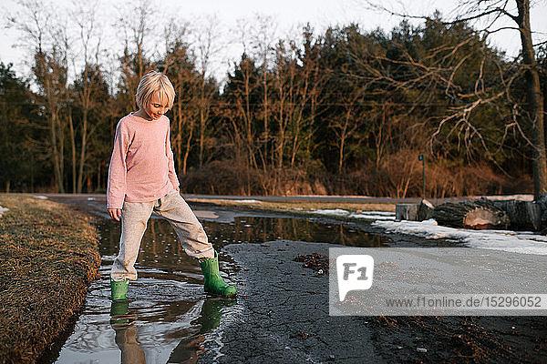 Junge tritt mit dem Knöchel tief in eine ländliche Schmelzwasserpfütze