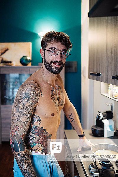 Mittelgroßer erwachsener Mann mit tätowierter Brust bei der Frühstücksvorbereitung  Porträt