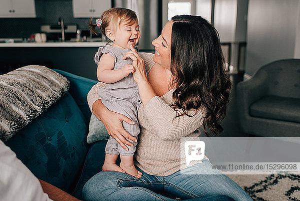 Mutter spielt mit der kleinen Tochter auf dem Sofa