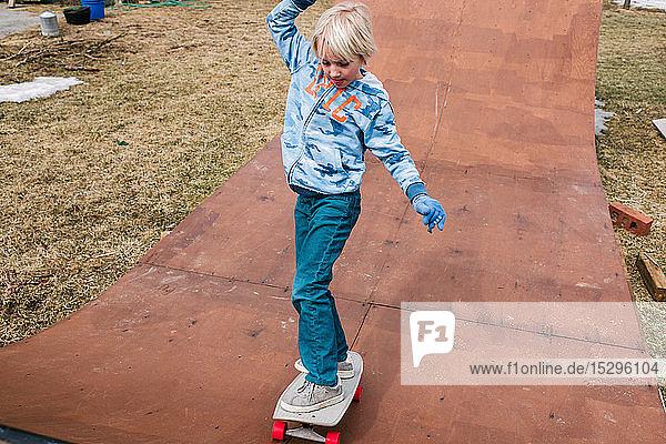 Jungen skateboarden auf hölzerner Skateboard-Rampe