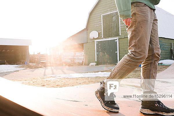 Mann geht über die Skateboard-Rampe auf dem Bauernhof  Taille nach unten