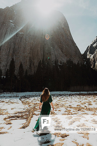 Young woman in long dress standing in sunlit snow covered mountain landscape  rear view  Yosemite Village  California  USA