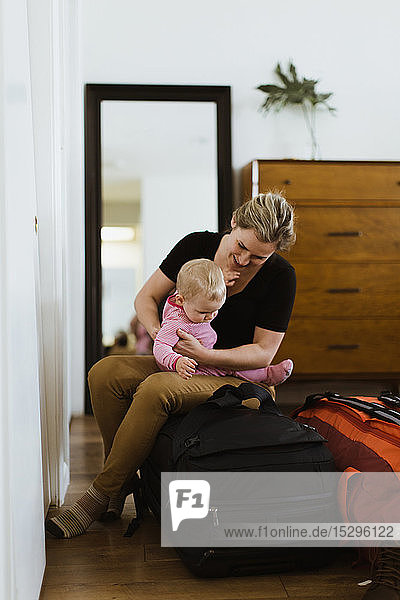 Mother on luggage with baby in bedroom