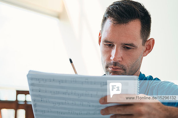 Mid adult man reading acoustic guitar sheet music  close up