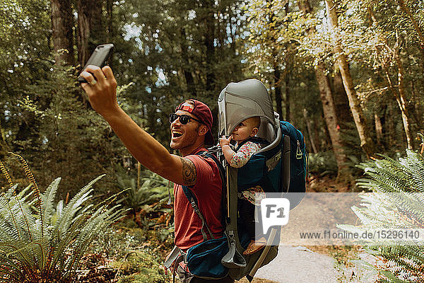 Father with baby taking selfie in forest  Queenstown  Canterbury  New Zealand